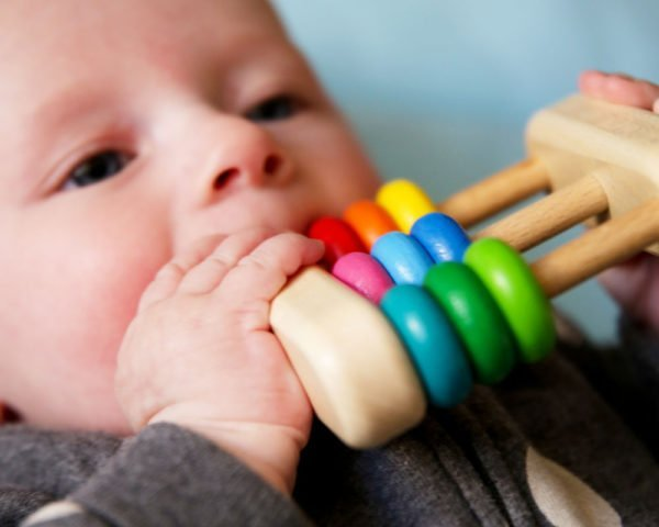 Baby holding wooden abacus rattle