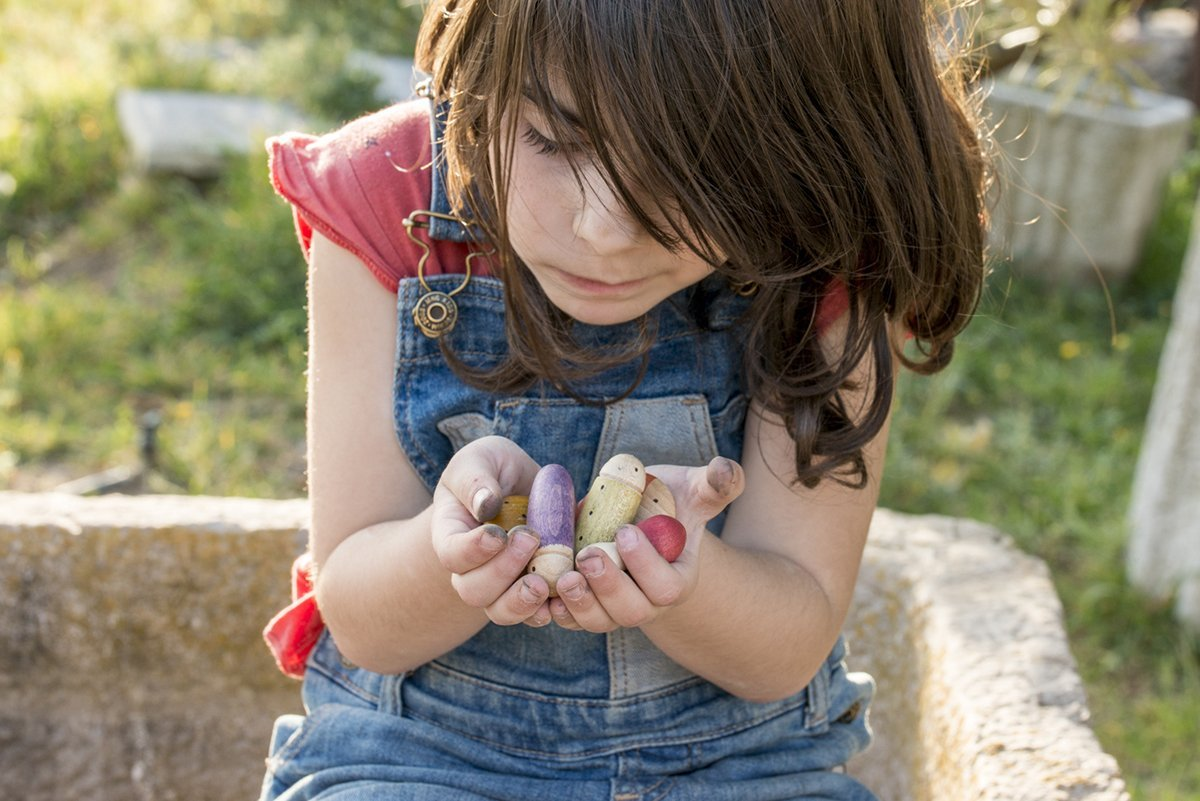 Child holding coloured wooden play pieces
